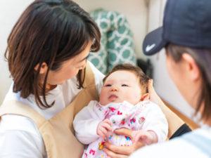 赤ちゃんを託児スタッフに預ける様子